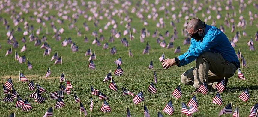 The U.S. hit a tragic milestone Tuesday, recording more than 200,000 coronavirus deaths. Here, Chris Duncan, whose mother, Constance, 75, died from COVID-19 on her birthday, visits a COVID Memorial Project installation of 20,000 American flags on the National Mall. The flags are on the grounds of the Washington Monument, facing the White House. (photo: Win McNamee/Getty Images)