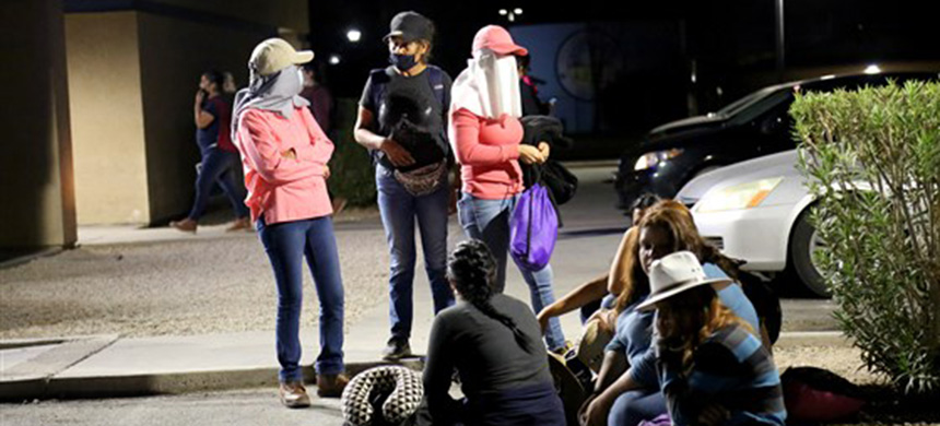 Migrant and seasonal day laborers gather outside a Chase parking lot to wait for buses that will take them to work on agricultural fields several miles away. (photo: Christine Romo/NBC News)
