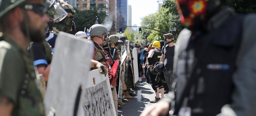 Rightwing and leftwing protesters battle with mace, paint balls and rocks near Justice Center in downtown Portland Saturday, 22 August 2020. (photo: Brooke Herbert/AP)