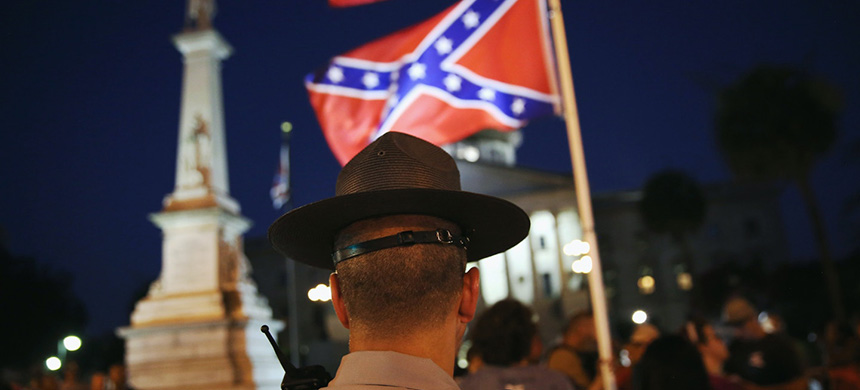 A highway patrolman stands guard as the 'Stars and Bars' Confederate flag flies in front of the South Carolina statehouse on July 9, 2015, in Columbia. (photo: John Moore/Getty Images)