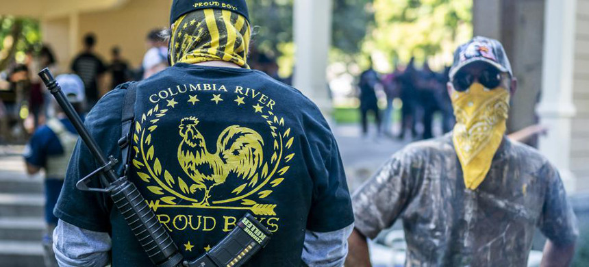 Armed members of the far-right Proud Boys groups stand guard during a memorial for Patriot Prayer. (photo: Getty Images)