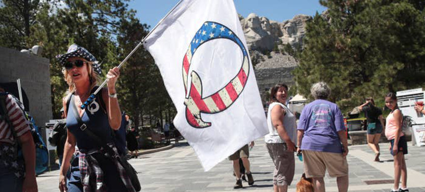 A Donald Trump supporter holds a QAnon flag at Mount Rushmore National Monument on July 1. (photo: Scott Olson/Getty)