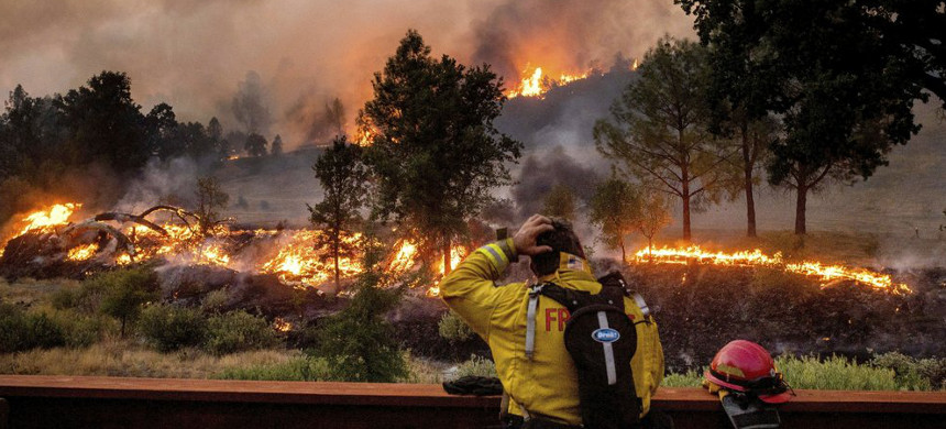 In this Aug. 21, 2020 file photo, a firefighter rubs his head while watching the LNU Lightning Complex fires spread through the Berryessa Estates neighborhood of unincorporated Napa County, California. (photo: Noah Berger/AP)
