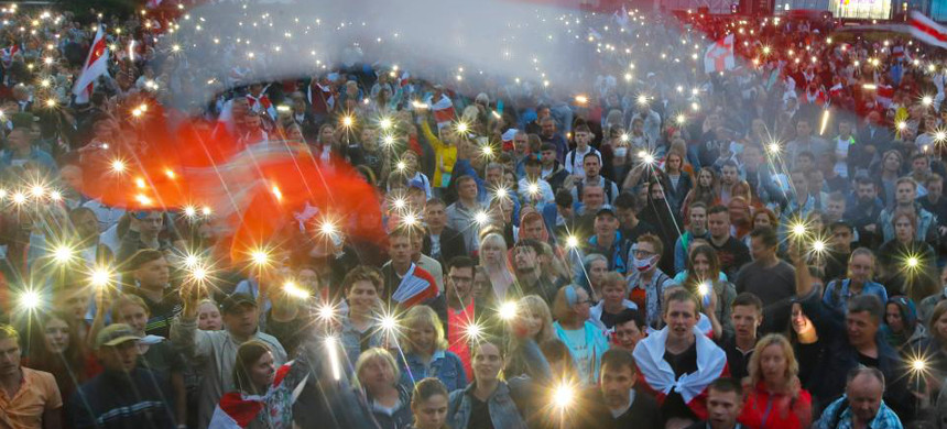 Belarusian opposition supporters light phones lights and wave an old Belarusian national flags during a protest rally in front of the government building at Independent Square in Minsk, Belarus, August 19, 2020. (photo: Dimitri Lovetsky/AP)
