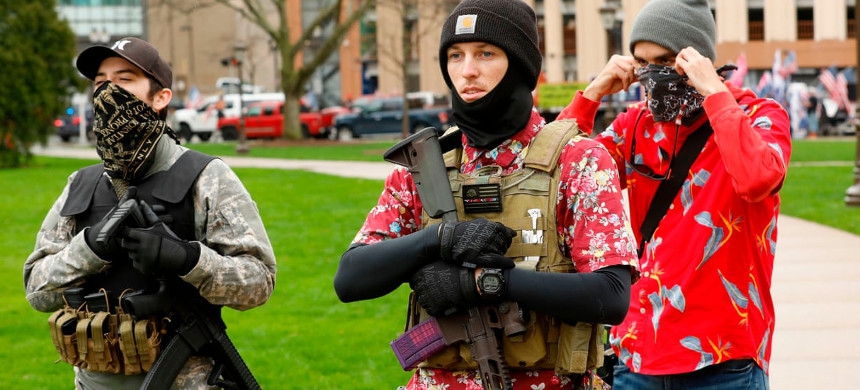 Armed protesters provide security for a protest demanding reopening in Lansing, Michigan, on 30 April. Members of the 'boogaloo' movement wear Hawaiian shirts paired with body armor and a military-style rifle. (photo: Jeff Kowalsky/Getty)