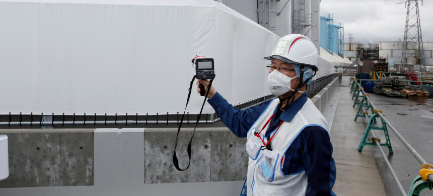A staff member of Tokyo Electric Power Company measures radiation levels around the storage tanks of radiation-contaminated water at the tsunami-crippled Fukushima Dai-ichi nuclear power plant in Okuma, Fukushima prefecture. (photo: AFP)