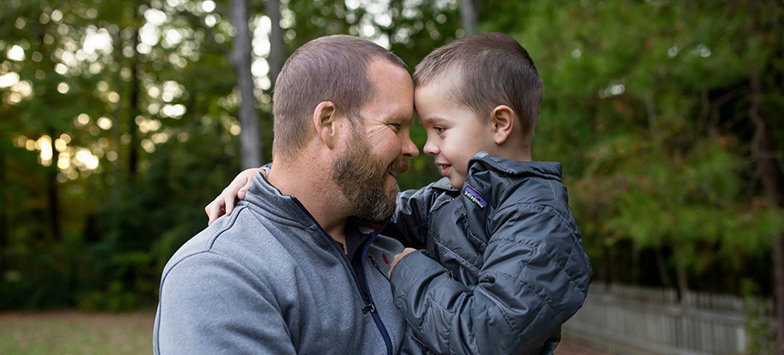 Mark Collie and his son Blake at home in Washington, N.C. When Blake suffered an aneurysm, Mr. Collie turned to a Christian health cost-sharing ministry to help cover the costs. (photo: Madeline Gray/NYT)