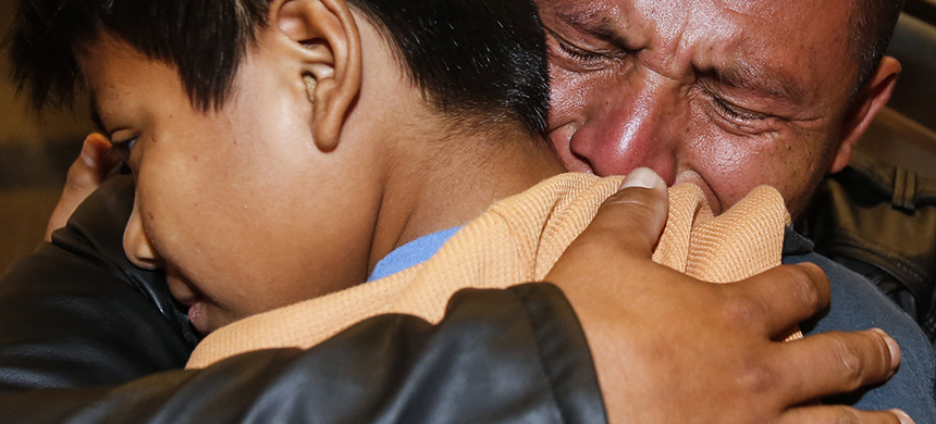 David Xol of Guatemala hugs his son Byron as they were reunited at Los Angeles International Airport in January. The father and son were separated 18 months earlier under the Trump administration's 'no tolerance' migration policy. (photo: Ringo H.W. Chiu/AP)