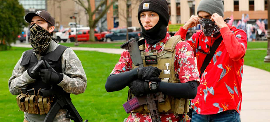 Armed protesters provide security for a protest demanding reopening in Lansing, Michigan, on 30 April. Members of the 'boogaloo' movement wear Hawaiian shirts paired with body armor and a military-style rifle. (photo: Jeff Kowalsky/AFP/Getty Images)