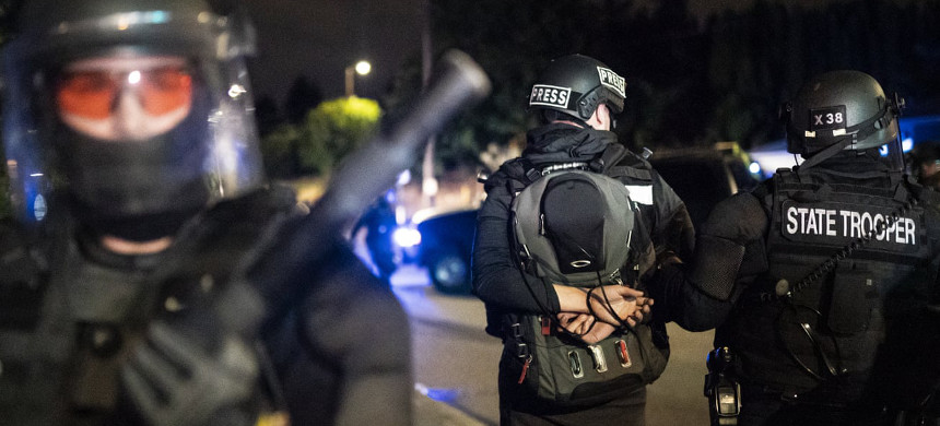 An Oregon State Trooper arrests a journalist during a crowd dispersal near the Portland east police precinct on August 30 in Portland, Oregon. (photo: Nathan Howard/Getty)