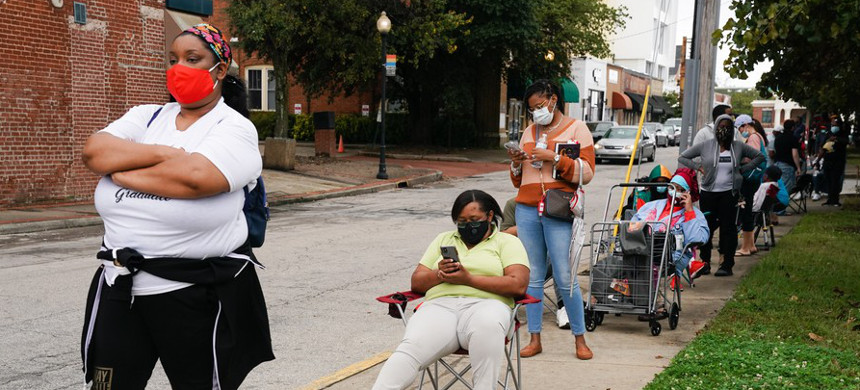 Residents wait in line outside an early voting polling location for the 2020 presidential election in Atlanta, Georgia, Monday, Oct. 12, 2020. (photo: Elijah Nouvelage/Bloomberg)