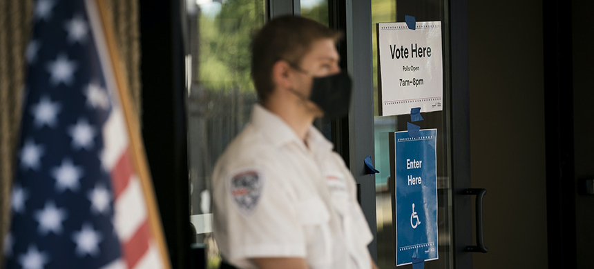 A security guard wears a protective mask while sitting outside a polling location in Minneapolis, Minnesota, on Tuesday, Aug. 11, 2020. (photo: Ben Brewer/Bloomberg/Getty Images)