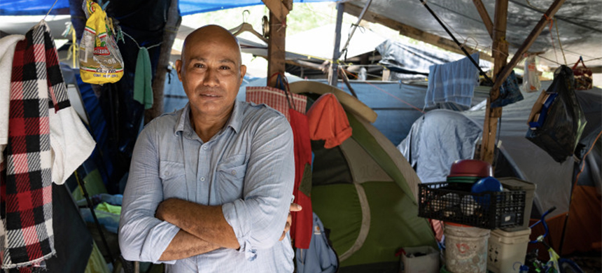 Dison poses for a photograph inside a wooden structure providing shelter over his tent in the camp in Matamoros, Northern Mexico. (photo: Lexie Harrison-Cripps/Al Jazeera)