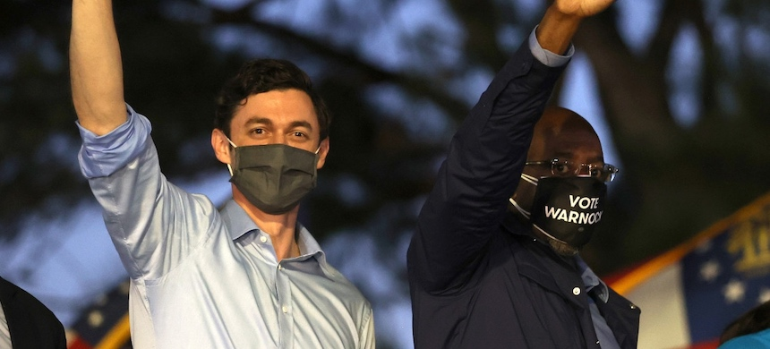 Democratic U.S. Senate candidates Jon Ossoff (L) and Rev. Raphael Warnock (R) wave to supporters during a 'Get Out the Early Vote' drive-in campaign event. (photo: Justin Sullivan/Getty Images)