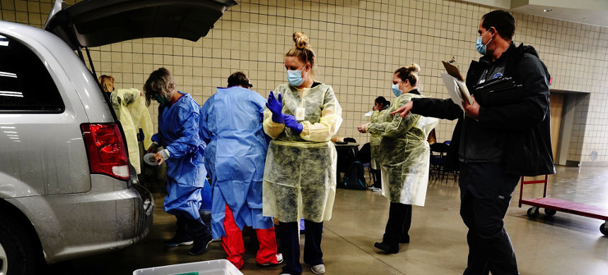 Nurses and healthcare workers don personal protective equipment before beginning their shifts at a drive-thru testing site inside the Bismarck Event Center in Bismarck, N.D., on Oct. 26, 2020. (photo: Bing Guan/Reuters)