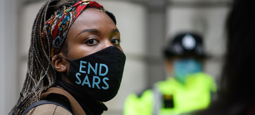 A woman wearing an 'END SARS' face mask outside the Nigerian Consulate during a demonstration in London, England. (photo: Leon Neal/Getty Images)