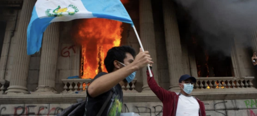 A demonstrator outside the congress building in Guatemala City during clashes between police and protesters on Saturday. (photo: Al Jazeera)
