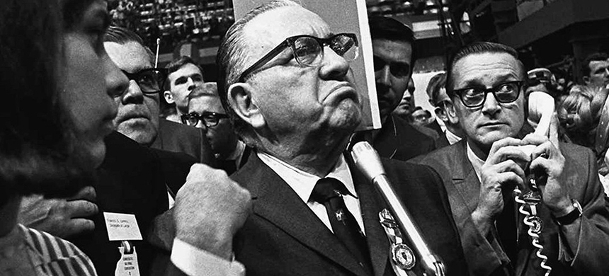Mayor Richard J. Daley stands at the microphone during the 1968 Democratic National Convention in Chicago, while shouts resound from the crowd. (photo: Jack Thornell/AP)