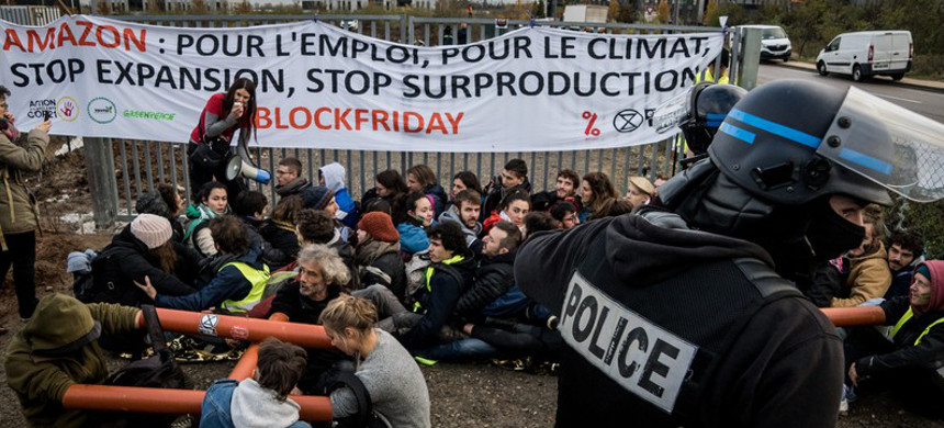 Protesters from environmentalist groups, including Extinction Rebellion, ANV-COP 21 and Alternatiba, block an Amazon depot in Saint Priest, near Lyon, France, on Black Friday 2019. (photo: Nicolas Liponne/Getty)