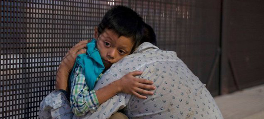 José, 27, embraces his son, José Daniel, 6, after crossing the border into the U.S. in El Paso, Texas, May 16, 2019. (photo: Paul Ratje/Getty)