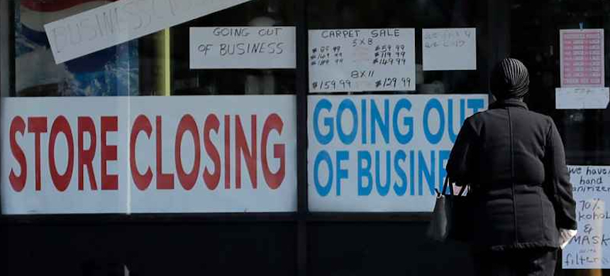 A woman looks at signs at a store closed due to COVID-19. (photo: Nam Y. Huh/AP)