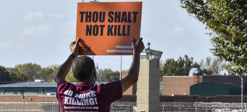 A protester holds a sign up across the street from the Federal Correctional Complex in Terre Haute, Indiana. (photo: Austen Leake/AP)