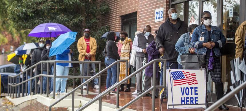 People wait in line on the first day of advance voting for Georgia's Senate runoff election at the Bell Auditorium in Augusta, Ga., Monday, Dec. 14, 2020. (photo: Michael Holahan/AP)