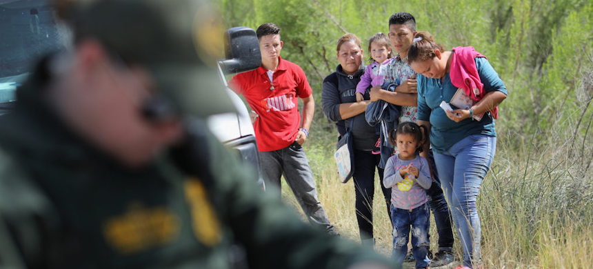 Central American asylum seekers wait as U.S. Border Patrol agents take groups of them into custody in June near McAllen, Texas. (photo: John Moore/Getty Images)