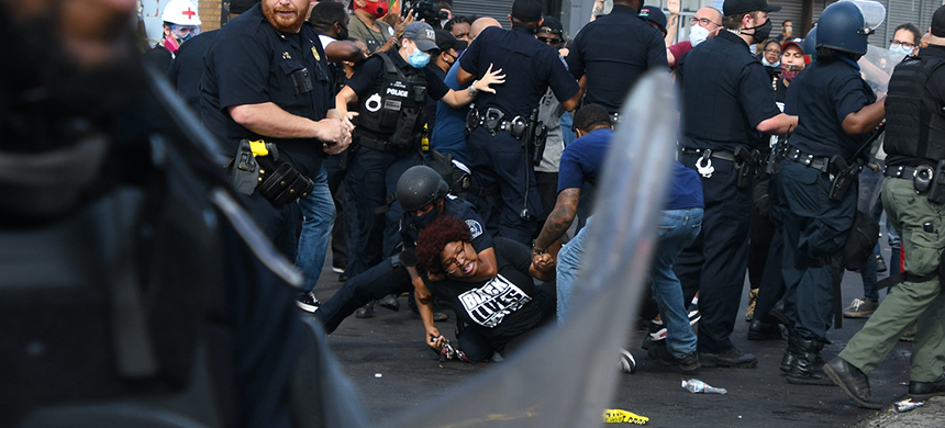 Nakia Wallace, an organizer with the activist organization Detroit Will Breathe, is placed in a chokehold by a Detroit police officer as riot police push into a crowd of protesters organized in response to the police shooting of Hakim Littleton on July 10, 2020. (photo: Adam J. Dewey)