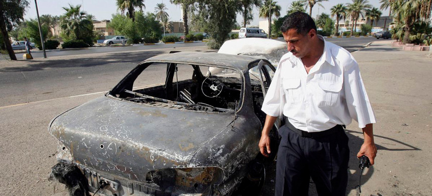 In this Sept. 25, 2007, photo, an Iraqi traffic policeman inspects a car destroyed by a Blackwater security detail in al-Nisoor Square in Baghdad, Iraq. (photo: Khalid Mohammed/Ap)