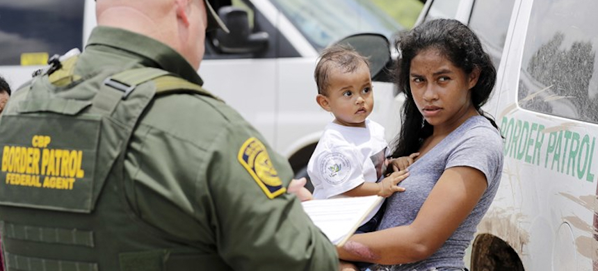 A mother from Honduras holds her child as they surrender to U.S. Border Patrol agents. (photo: David J. Phillip/AP)