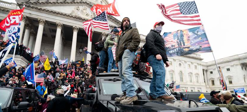 Trump supporters stand on the U.S. Capitol Police armored vehicle as others take over the steps of the Capitol. (photo: Bill Clark/Congressional Quarterly/ZUMA)