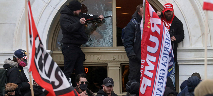 A man breaks a window as a mob of President Trump's supporters storms the U.S. Capitol on Jan 6. (photo: Leah Millis/Reuters)