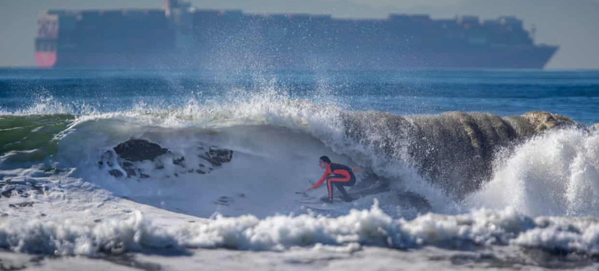 A surfer at Huntington beach on the Pacific coast of the US. Scientists expect about 1 metre of sea level rise by the end of the century. (photo: Allen J Schaben/Los Angeles Times/Rex/Shutterstock)