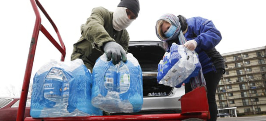 Rabbi Yosef Chesed, left, helps unload bottled water being donated by Lorie Lutz, right, at a Detroit food pantry in March. (photo: Paul Sancya/AP)
