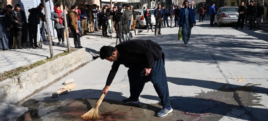 A resident washes a road after gunmen killed two female judges working for the Supreme Court in the capital. (photo: Wakil Kohsar/AFP)