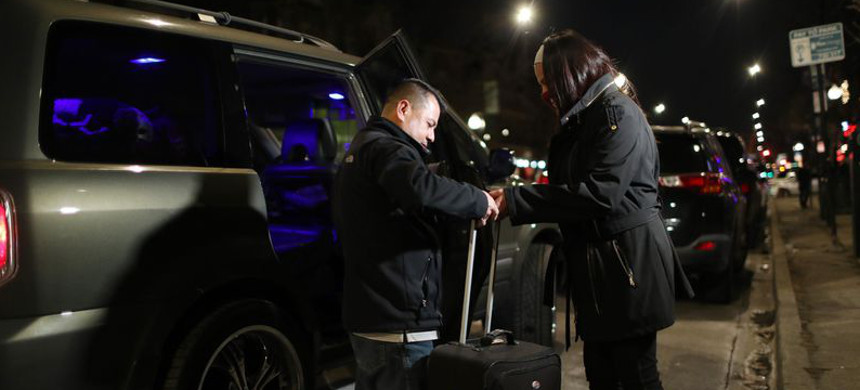 Francisca Lino hands luggage to her husband, Diego Lino, outside Adalberto Memorial United Methodist Church, 2716 W. Division St., as they head home to Romeoville on Jan. 23, 2021, in Chicago. (photo: John Kim/Chicago Tribune)
