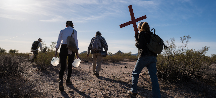 Artist and activist Alvaro Enciso, middle, leads a small group into the desert northwest of Tucson in to place handmade crosses where migrants lost their lives and to leave water for migrants making their way north and west. (photo: Max Herman)