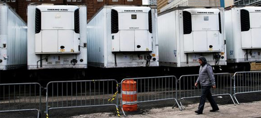 A man walks near a row of refrigeration units used as makeshift morgues located behind Bellevue Hospital as the Empire State Building is seen during the outbreak of the coronavirus disease (COVID-19) in New York City, U.S., March 31, 2020. (photo: Eduardo Munoz/Reuters)