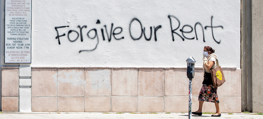 A woman wearing a mask walks past a wall bearing a graffiti asking for rent forgiveness amid the COVID-19 pandemic. (photo: Valeria Macon/AFP/Getty Images)