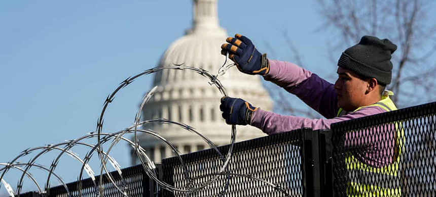 A worker removes razor wire from the top of security fencing on 20 March 2021, as part of a reduction in heightened security measures taken after the 6 January attack on the US Capitol in Washington DC. (photo: Joshua Roberts/Reuters)