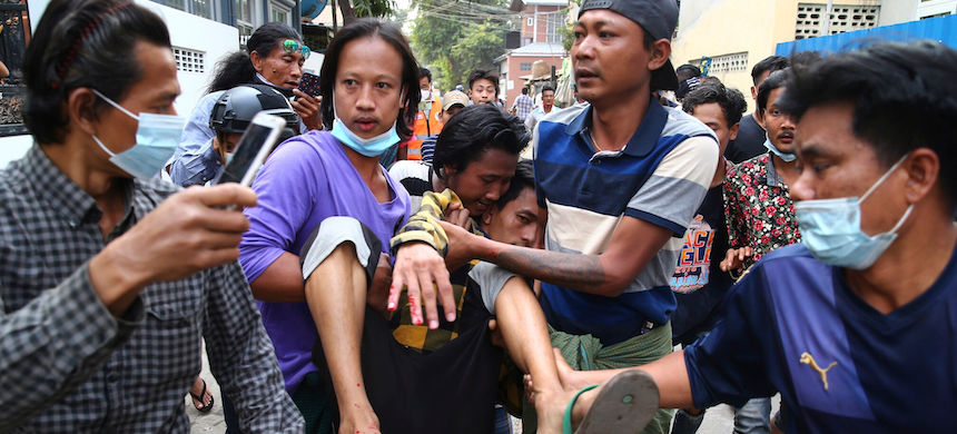 Protesters carrying an injured man in Mandalay, Myanmar. (photo: AP)