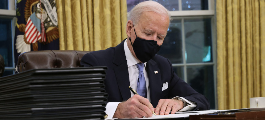 U.S. President Joe Biden prepares to sign a series of executive orders, including rejoining the Paris Climate Agreement. (photo: Chip Somodevilla/Getty)