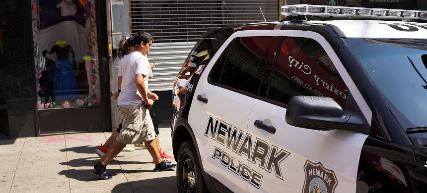 People walk by a police car downtown on May 13, 2014, in Newark, New Jersey. (photo: Spencer Platt/Getty)