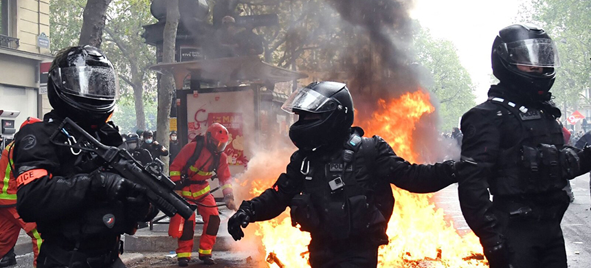 Police officers walk near a fire burning in the street during May Day protests in Paris on Saturday. (photo: Bertrand Guay/Getty Images)
