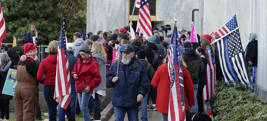 Pro-Trump and anti-mask demonstrators hold a rally outside the Oregon state capitol as legislators meet for an emergency session in Salem, Oregon, on 21 December 2020. (photo: Andrew Selsky/AP)