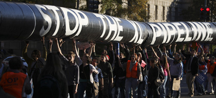 A mock oil pipeline is carried during a Keystone XL tar-sands oil pipeline demonstration near the White House, 11/06/11. (photo: Andrew Harrer/Bloomberg)