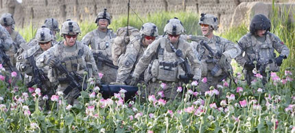 A fallen American soldier is carried through a field of poppies to a helicopter evacuation site, 06/17/11. (photo: Paula Bronstein/Getty Images)