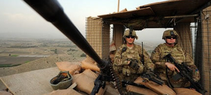 US soldiers stand guard on a watchtower overlooking villages in Khost Province, Afghanistan, 06/21/11. (photo: Ted Aljibe/AFP/Getty Images)