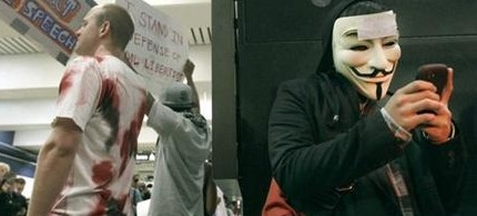 An unidentified protester wearing a Guy Fawkes mask uses his cell phone during a protest at the Civic Center BART station in San Francisco, 08/15/11. (photo: Jeff Chiu/AP)